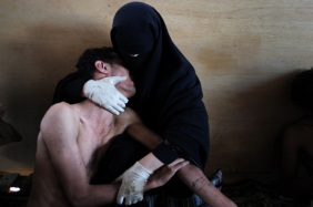 A woman holds a wounded relative in her arms, inside a mosque used as a field hospital by demonstrators against the rule of President Ali Abdullah Saleh, during clashes in Sanaa, Yemen on 15 October 2011. - ©Samuel Aranda for The New York Times - World Press Photo of the Year