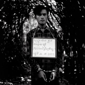 A poacher photographed and questioned in Cambodia. The nature and date of his crime was written on a board around his neck, 2002. ©Patrick Brown/Panos Pictures